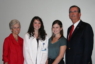 Sarah and Jim Ainsworth stand beside two female scholarship recipients.