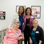 Leigh Ann Ross and Lauren Bloodworth stand and smile behind two older female patients
