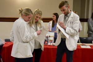 Two female student pharmacists and a male student pharmacist stand in a circle filling out papers
