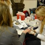 A female student pharmacists takes blood from female patient's finger