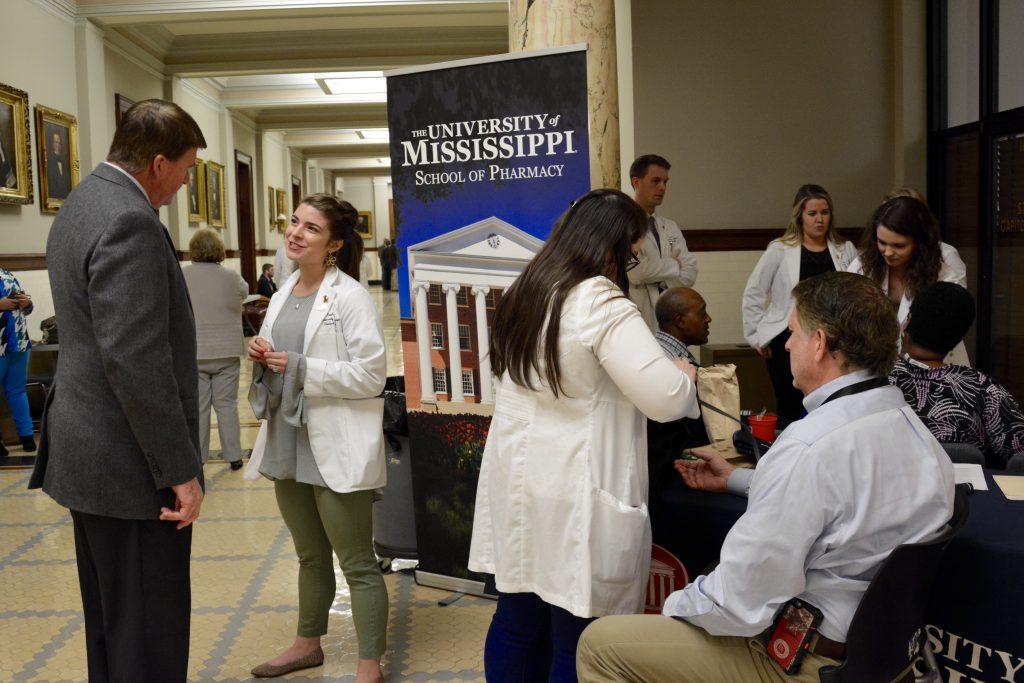 Student pharmacists assists male legislators with health screenings