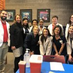10 student pharmacists and a female administrator gather for a group photo