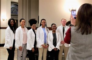 Six student pharmacists in their white coats, stand in a row, smiling for someone taking picture with  phone
