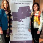 Leigh Ann Ross and Lauren Bloodworth stand smiling in front of a banner.