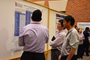 Three men looking at research findings on poster