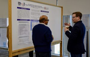 Two men talking and looking at a research poster.