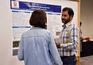 A man and woman talking and looking at a research poster.