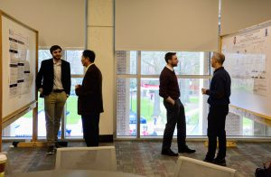 Four men, talking in pairs, about research posters beside them.