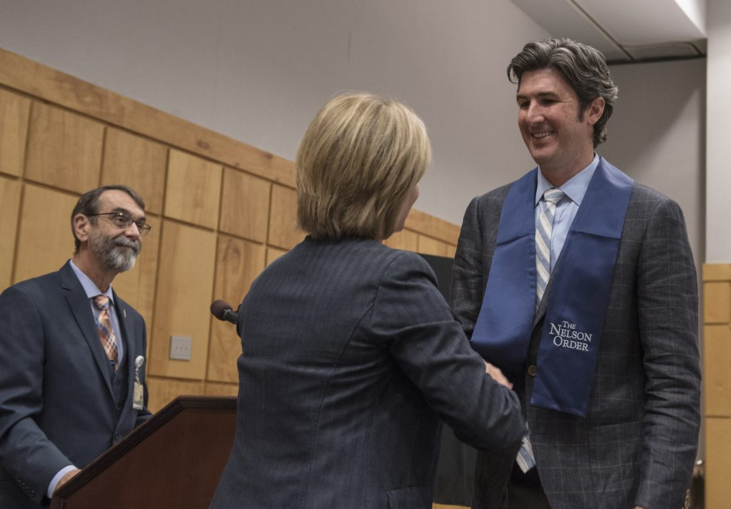 University of Mississippi Vice Chancellor for Health Affairs LouAnn Woodward inducts School of Pharmacy professor Josh Fleming into the Nelson Order for teaching excellence.