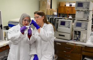 Pharmaceutics graduate students Tabish Mehraj (left) and Corinne Sweeney (right) work with equipment that will be integral to the new Master's of Industrial Pharmacy program.