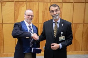 Scott Malinowski (left) is congratulated by Rob Rockhold, deputy chief academic officer for UMMC, during the 2018 Nelson Order ceremony.