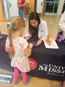 Lily Van works with a child at Mississippi Science Fest