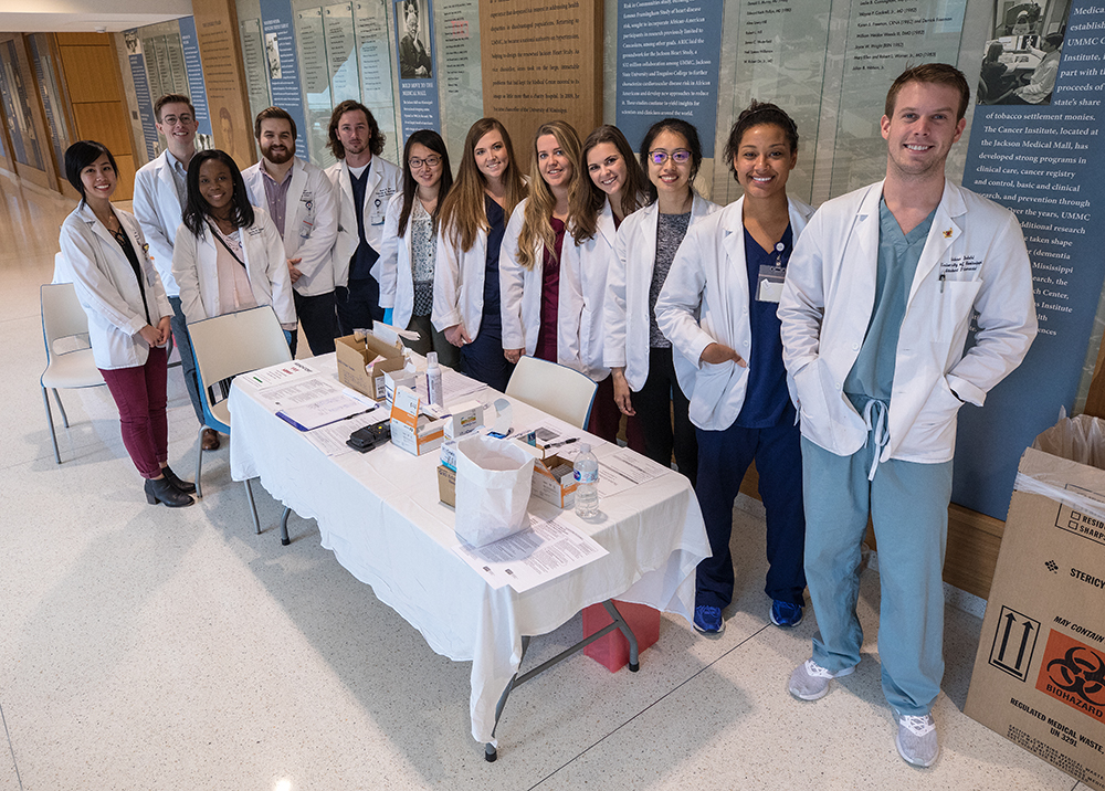 Group of student pharmacists standing behind a table