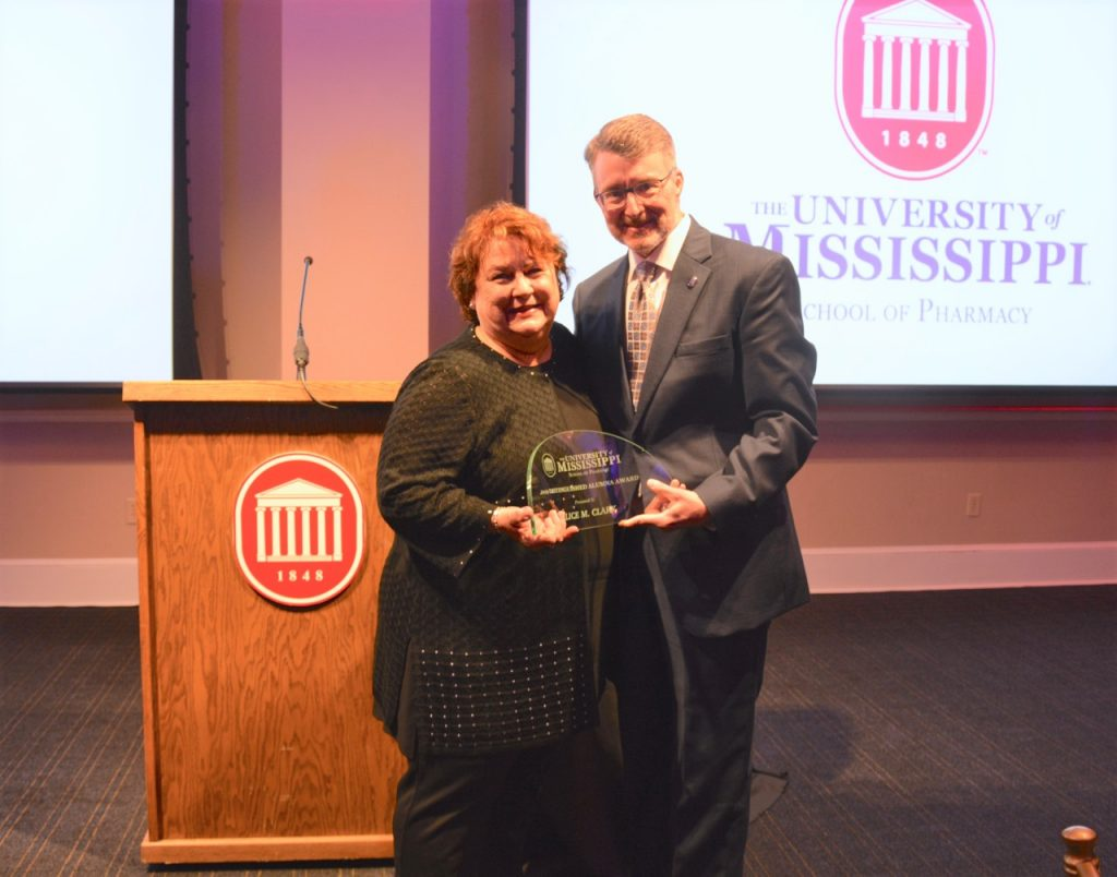 Alice Clark receives the Alumna of the Year award from Dean Allen.