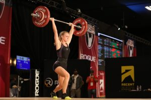 Emily Lewis lifting a weight above her head