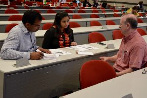 Two male and one female faculty member sit and discuss an activity.