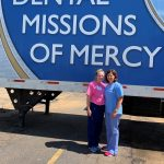 """Picture of two females standing outside in front of a semi-truck trailer that reads """"Dental Mission of Mercy"""""""