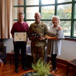 Dean Allen is presented with a certifacte and American flag from Major Bradley and his wife Dawn