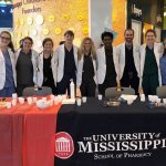 Nine student pharmacists in their white coats stand in a row, smiling