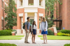 Three students stand outside of building, talking