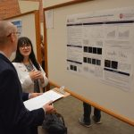 Female student presents her research to a male judge.