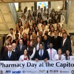 """Group of students and professionals stand on staircase holding sign """"Pharmacy Day at the Capitol"""""""