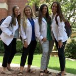 Four female students stand together in their white coats.