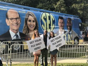 Three students hold signs in front of SEC Nation tour bus
