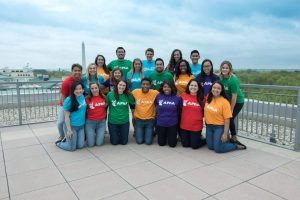 Group of students in multicolored shirts stand outside for group photo