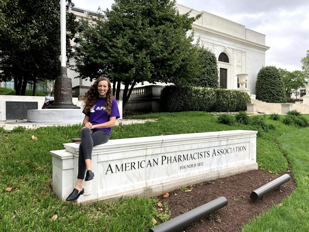 Miranda Craft sits on a building sign outside of the American Pharmacist Association.