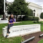 Miranda Craft sits on a building sign that reads American Pharmacist Association
