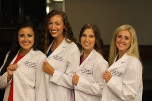 Four female student pharmacists show off their new white coats