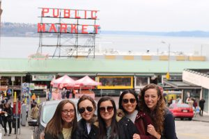 Five female students stand outside in front of Seattle's iconic Public Market sign