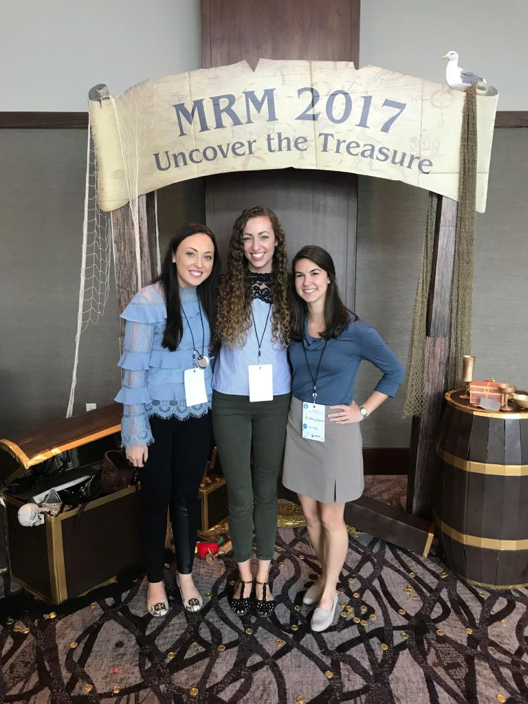 "Three female students standing under a sign ""MRM 2017 Uncover the Treasure"""