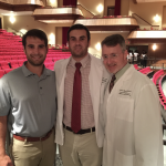 Austin and Blake Freeman stand with Dean David Allen inside a theater.