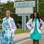 Washington and Fizer stand outside by Murrah High School sign in their white coats.
