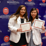 Two female students hold up their award certificates