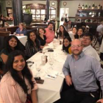 Group photo of people sitting at a table in a restaurant.