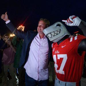 Tony the Landshark mascot posing with coach Lane Kiffin