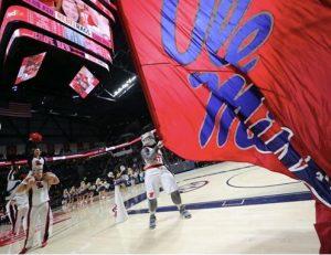 Tony the Landshark mascot waves an Ole Miss flag on the basketball court.