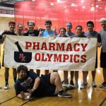 """Group of students gather together with a banner """"Pharmacy Olympics"""""""