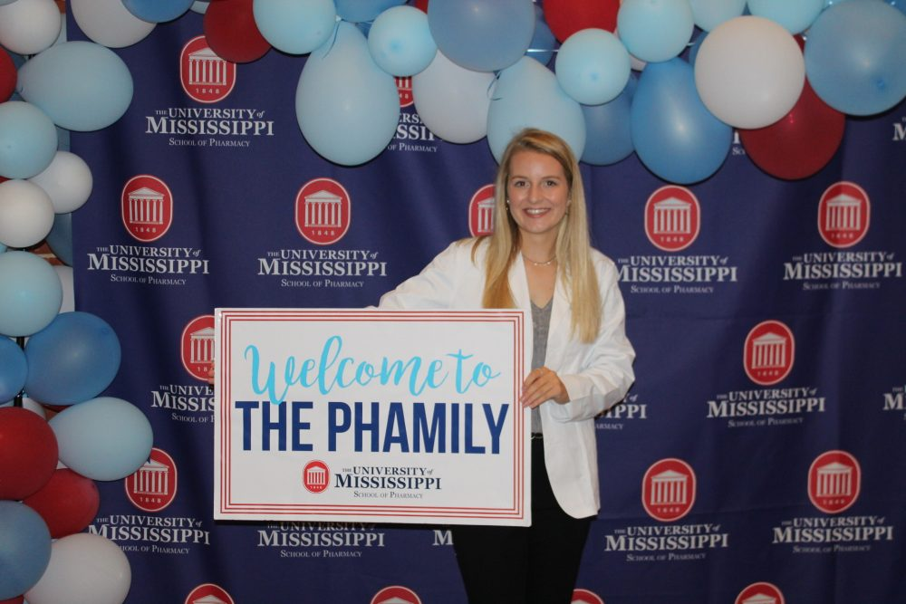 """Abby Fischer holds a sign that says """"Welcome to the Phamily"""""""