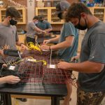 A group of male students work on cages to catch oysters