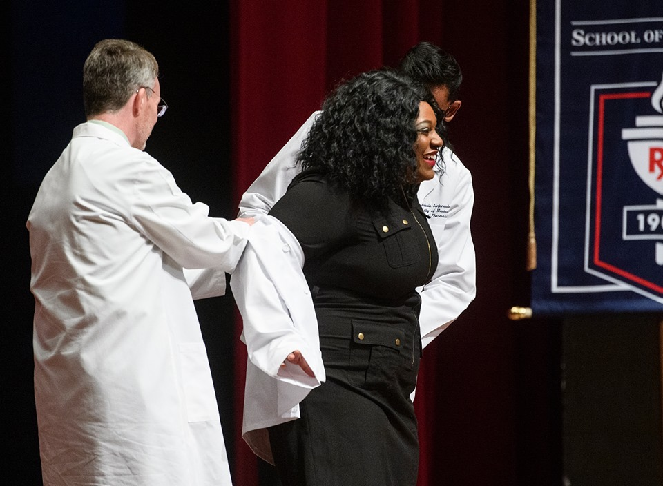 Alexcia receives help putting on her white coat for the first time.