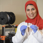 Rasha Elkanayati holds up her dry mouth strip product with lab equipment in background.