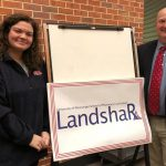 Two people standing beside sign that says 'LandshaRx'