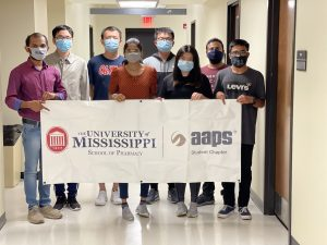Group of graduate students in masks holding a sign
