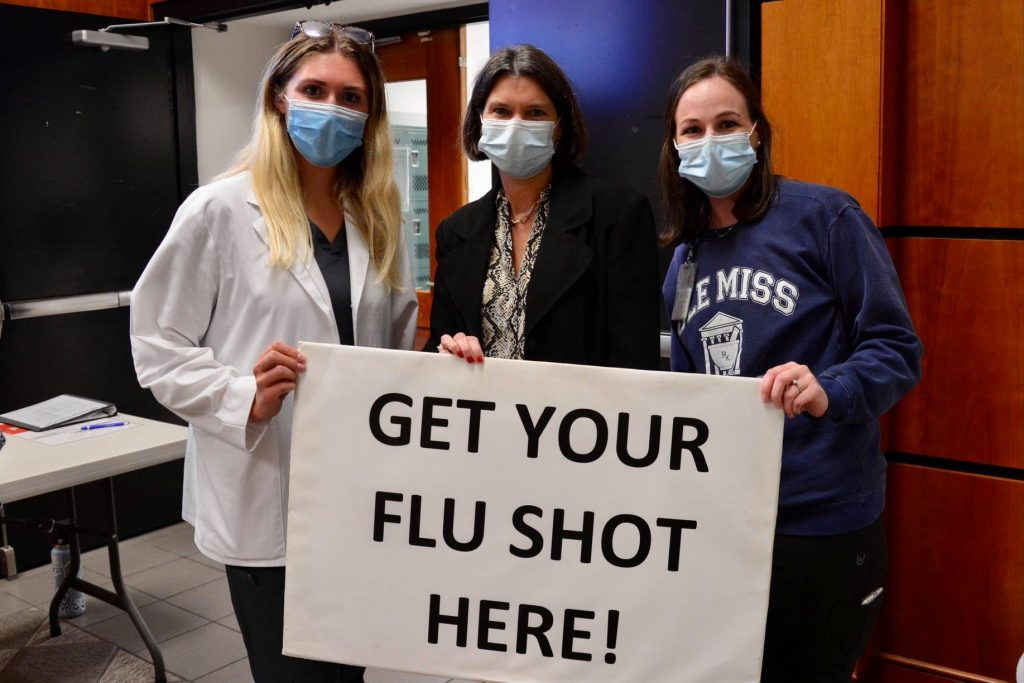 """Two female students stand with administrator Donna Strum holding sign """"Get Your Flu Shot here!"""""""