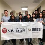11 students stand for a group photo, holding banner with school and organization logo