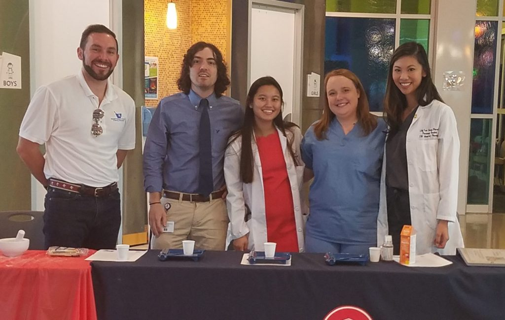 Five pharmacy residents stand together behind a table at a children's museum event.